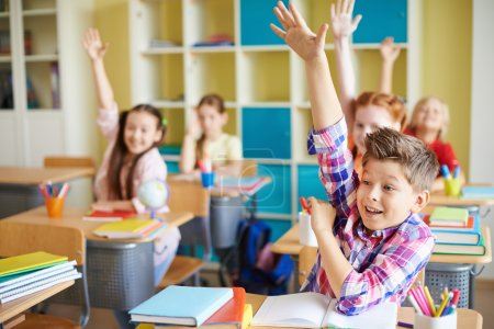 Boy raising hand at workplace with classmates