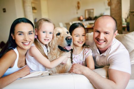 Photo for Happy family of four with dog looking at camera at home - Royalty Free Image