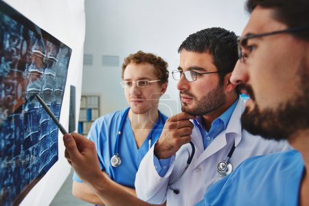 Photo for Young male doctors looking attentively at x-ray and discussing it - Royalty Free Image