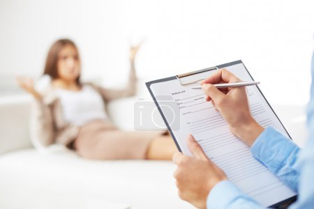 Photo for Professional psychiatrist consulting her patient and making notes in application form - Royalty Free Image