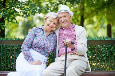 Photo for Happy seniors sitting on bench in the park and looking at camera - Royalty Free Image