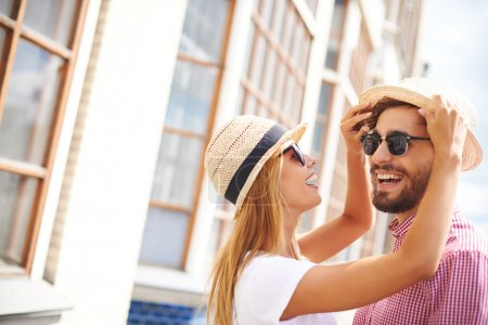 Photo for Happy girl and her boyfriend in hats and sunglasses enjoying their being together - Royalty Free Image