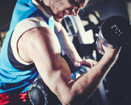 Photo for Arm of strong man doing exercise with barbell - Royalty Free Image