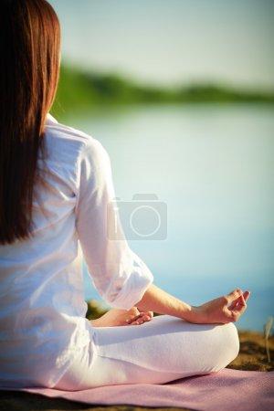 Woman relaxing in pose of lotu