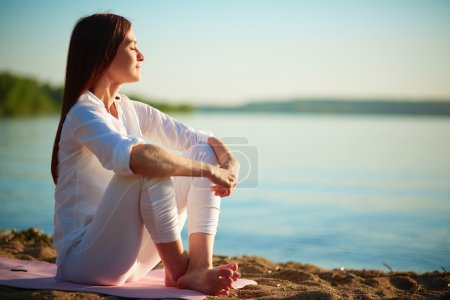 Photo for Side view of serene woman sitting on sandy beach against blue sky outdoors - Royalty Free Image