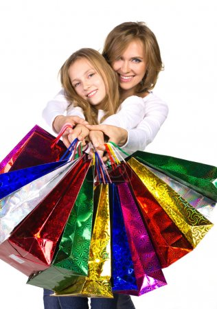 Photo for Mother and daughter holding out many shopping bags isolated on white - Royalty Free Image
