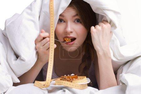 Photo pour Belle jeune fille manger gâteau éponge sous couverture blanche sur fond blanc - image libre de droit