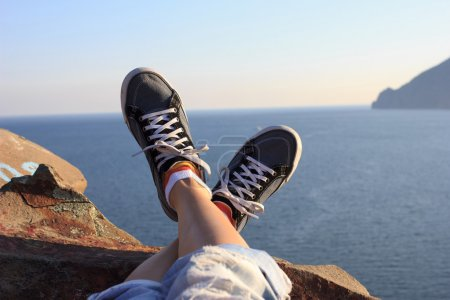 Photo for Legs in sneakers on seascape background - Royalty Free Image