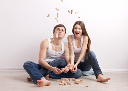 Young man and woman sitting on floor in new apartm...