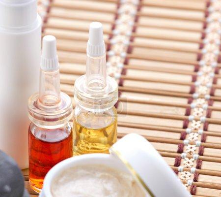 Photo pour Produits cosmétiques pour le visage et le corps sur tapis de bambou sur fond flou - image libre de droit