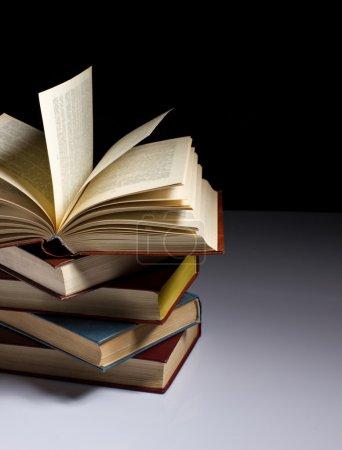 Photo pour La pile de vieux livres sur la table, sur fond foncé - image libre de droit