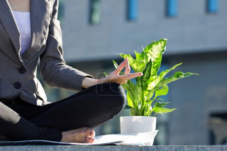 Photo for Closeup of meditating businesswoman in yoga lotus pose outdoors, near green flower in pot, blurred building background - Royalty Free Image