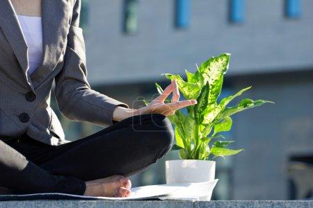 Photo pour Gros plan de femme d'affaires méditation en posture de lotus yoga en plein air, près de fleur verte en pot, floue fond de bâtiment - image libre de droit