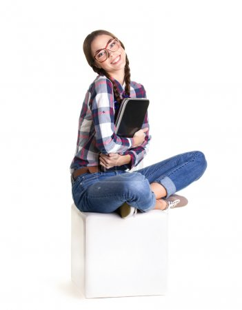 Photo for Happy girl sitting with cross-legged holding notebook and look at camera  on white background - Royalty Free Image