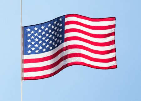 American flag in the wind against a blue sky