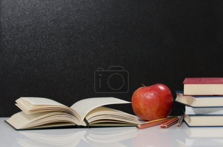 Photo for Blackboard, pencils, books and an apple - Royalty Free Image