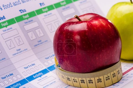 Photo for Green and red apples with a measuring tape and programs written about food and activity char - Royalty Free Image