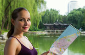 Young tourist woman holding map. Student travel in China