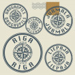 Grunge rubber stamp set with names of Latvian citi...