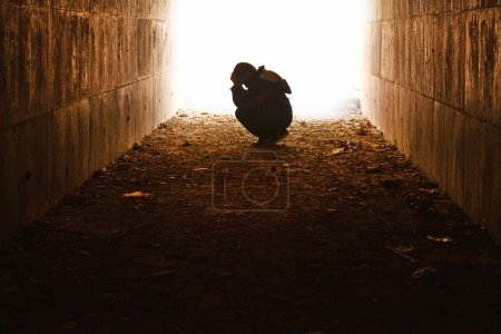 waif sitting in the tunnel in sorrow