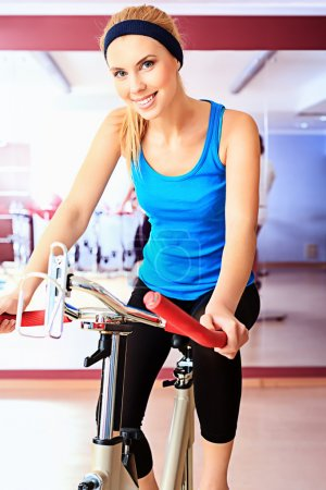 Photo for Young sporty woman doing exercise on bicycle in the gym centre. - Royalty Free Image