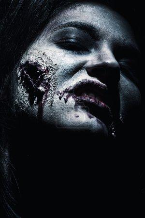 Foto de Primer plano de un zombi sediento de sangre sobre fondo negro. - Imagen libre de derechos
