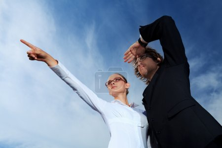 Photo for Successful business standing over blue sky and purposefully looking away. - Royalty Free Image