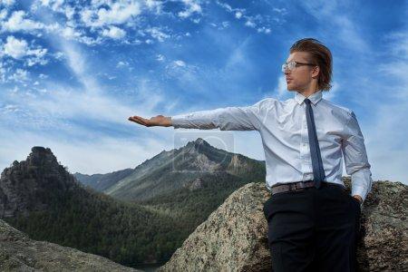 Photo pour Homme d'affaires réussie debout sur un sommet de la montagne et délibérément à la recherche.. - image libre de droit
