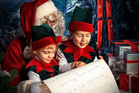 Photo for Santa Claus sitting with two little cute elves over Christmas background. - Royalty Free Image