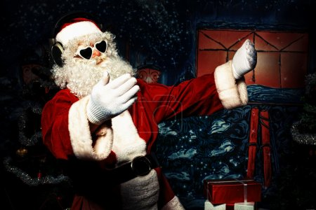 Photo for Santa Claus is listening to music in headphones. Christmas. - Royalty Free Image