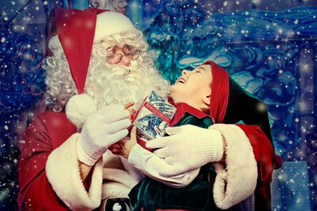 Photo for Santa Claus sitting with a little cute boy elf over Christmas background. - Royalty Free Image