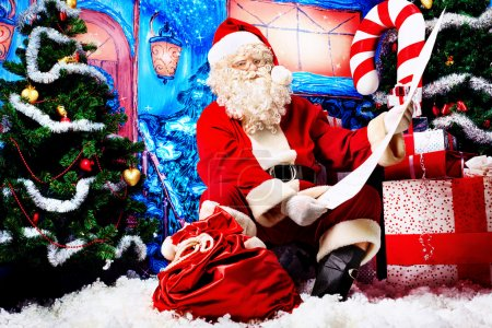 Photo for Santa Claus posing with a list of presents over Christmas background. - Royalty Free Image