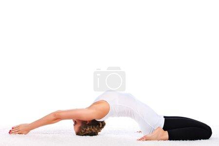 Photo pour Jeune femme mince faisant de l'exercice de yoga. Isolé sur fond blanc . - image libre de droit