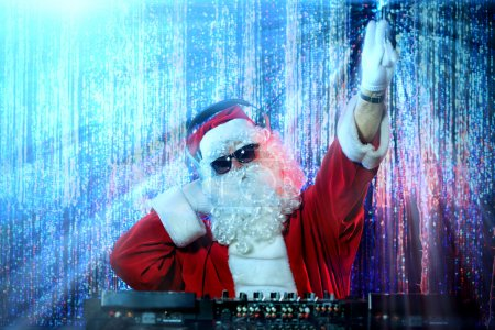 Photo for DJ Santa Claus mixing up some Christmas cheer. Disco lights in the background. - Royalty Free Image