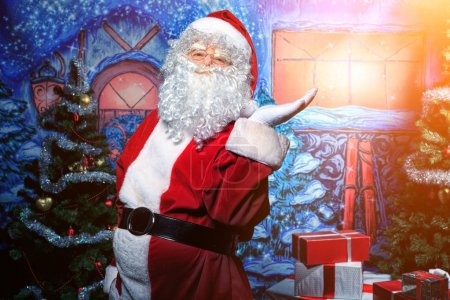 Photo for Santa Claus posing with presents over Christmas background. - Royalty Free Image