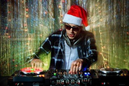 Photo pour DJ mélanger vers le haut de quelque joie de Noël. lumières Disco en arrière-plan. - image libre de droit