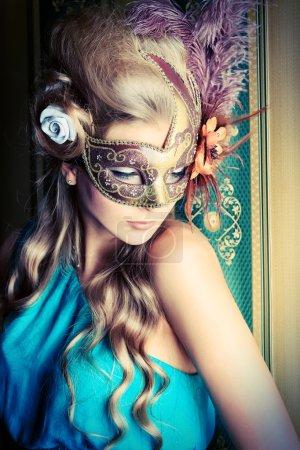 Photo pour Belle jeune femme dans un masque de carnaval sur fond vintage . - image libre de droit