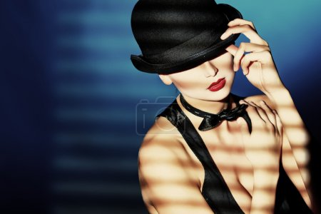 Photo for Elegant young woman posing in vest and black pot hat. Light and shadow. - Royalty Free Image