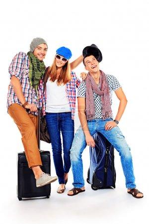 Foto de Grupo de alegre joven parado junto con las maletas sobre fondo blanco. - Imagen libre de derechos
