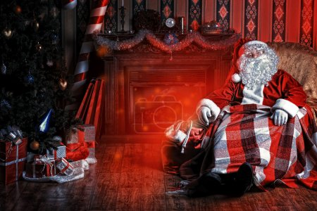 Photo for Santa Claus having a rest in a comfortable chair near the fireplace at home. - Royalty Free Image