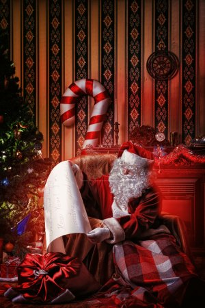 Photo for Santa Claus with a list of Christmas presents sitting in a comfortable chair near the fireplace at home. - Royalty Free Image