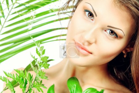 Photo for Beautiful young woman with perfect skin standing among fresh green leaves. Isolated over white background - Royalty Free Image