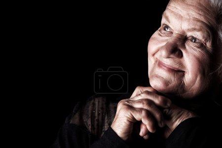 Photo pour Portrait d'une heureuse femme âgée souriant à la caméra. Sur fond noir . - image libre de droit