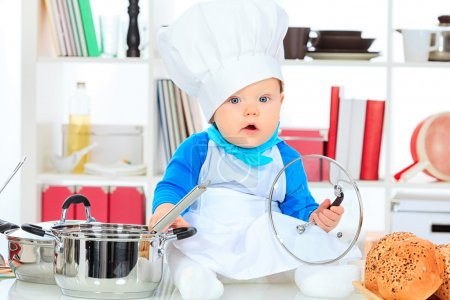 Photo for Cute small baby in the cook costume at the kitchen. - Royalty Free Image