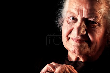 Photo for Portrait of a happy senior woman smiling at the camera. Over black background. - Royalty Free Image
