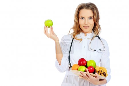 Photo for Portrait of a smiling woman doctor holding fresh fruits. Isolated over white background. - Royalty Free Image