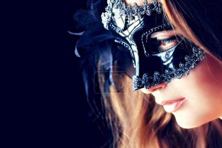 Photo pour Portrait d'une belle jeune femme dans un masque de carnaval. Sur fond noir . - image libre de droit