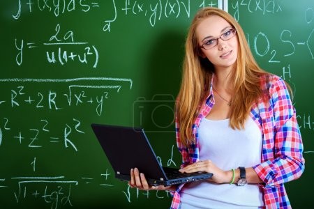 Photo for Pretty student girl standing at the blackboard in the classroom. - Royalty Free Image