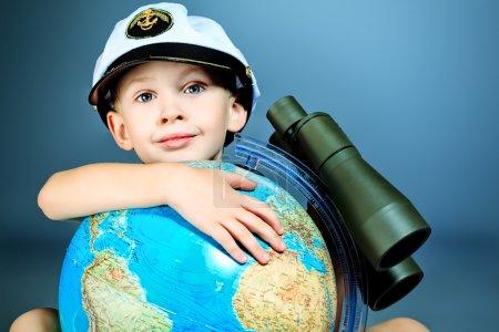 Photo pour Petit marin assis avec le globe et jumelles . - image libre de droit