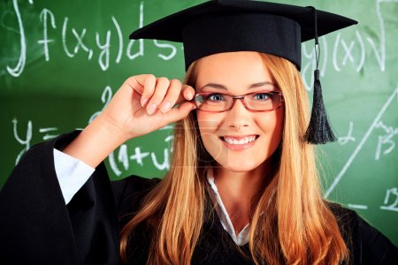 Photo for Portrait of a graduating student girl in an academic gown standing at the classroom. - Royalty Free Image
